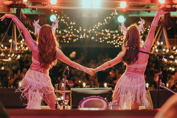 Two dancers hold hands while performing on the Brewhemia stage during Christmas party nights
