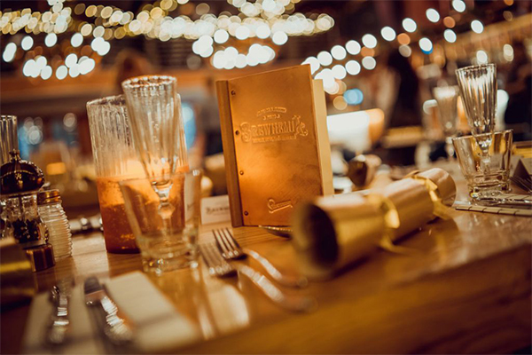 A set table features the Brewhemia drinks menu, glasses of champagne and gold Christmas Crackers