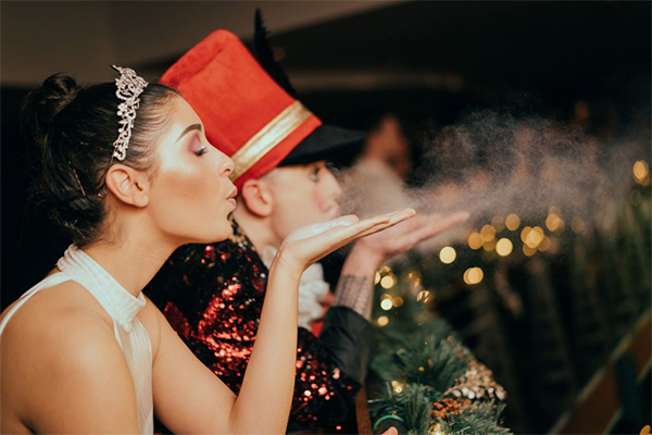 Two performers blow festive spirit into the air during a Christmas show at Brewhemia Edinburgh