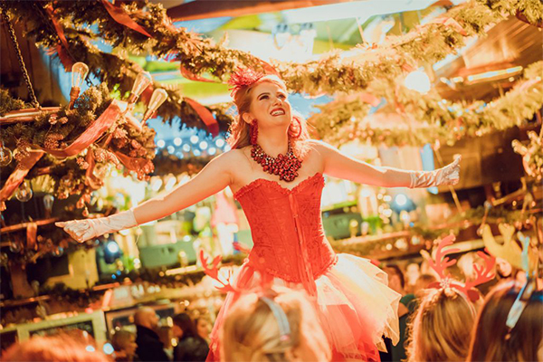 A Brewhemia performer stands on the table, under the festive lights and decor in the Beer Palace during a Christmas show