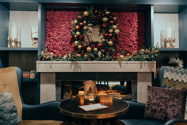 A Christmas wreath is displayed above the fireplace in the Brewhemia Caffe