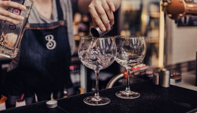 Bar staff pour a measure of Gin into two goblets at a bar in Brewhemia