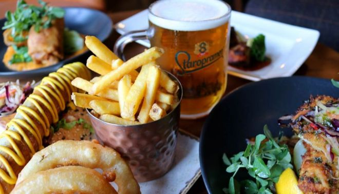 Chicken schnitzel, chips, onion rings and a bratwurst photographed alongside a Fresh pint of Staropramen beer at Brewhemia Edinburgh